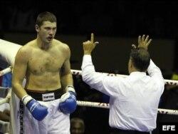 El árbitro hace un conteo de protección al boxeador ruso Dmitry Zaytsev (izq), antes de detener el combate con el cubano Erislandy Savón.
