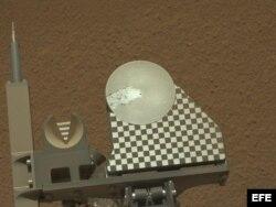 El brazo del robot Curiosity entrega una muestra de suelo marciano a la bandeja de observación del rover durante el 70 día de la misión marciana.