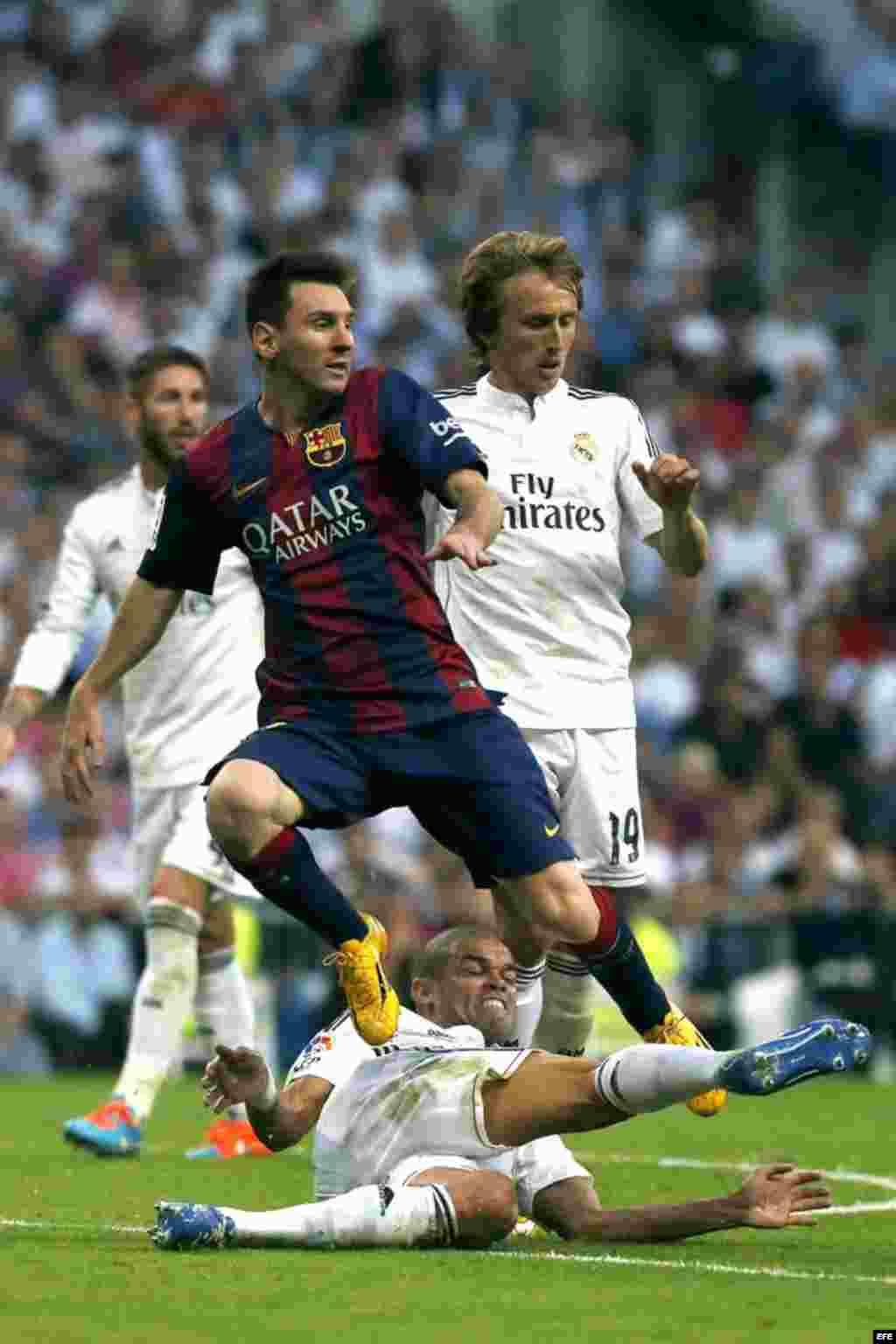 """El delantero argentino del FC Barcelona Lionel Messi (i) y el defensa portugués del Real Madrid Kléper Laveran """"Pepe"""" (abajo), durante el partido de la novena jornada de Liga de Primera División disputado el sábado 25 de octubre en el estadio Santiago Bernabéu."""