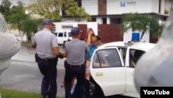 Un agente de la Seguridad del Estado y dos policías arrestan a la activista Ailer González.