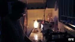 Una mujer lava los platos iluminada por una lámpara de queroseno en el habanero barrio de El Vedado. EFE