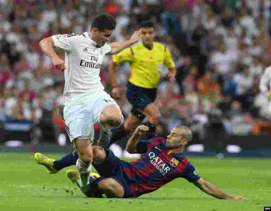 El defensa argentino del FC Barcelona Javier Mascherano (d) lucha un balón con el centrocampista colombiano del Real Madrid James Rodríguez (i).