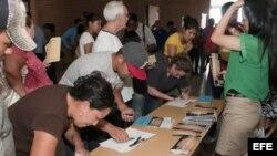Varios jóvenes indocumentados soñadores rellenan folletos y reciben información de unos voluntarios el 2 de julio 2012, durante un foro comunitario celebrado en Tucson, Arizona.