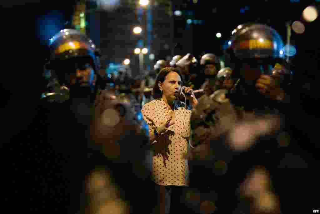 La esposa del alcalde mayor de Caracas Antonio Ledezma, Mitzy Capriles, habla por teléfono en medio de miembros de la Policía Nacional Bolivariana (PNB) que custodian el edificio del Servicio Bolivariano de Inteligencia Nacional (SEBIN) (19 de febrero, 2015).