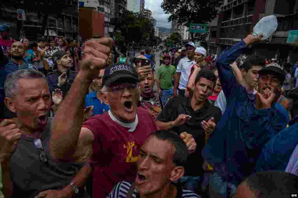 Un grupo de personas manifiestan contra miembros de la Guardia Nacional Bolivariana (GNB) hoy, jueves 2 de junio del 2016, en el centro de la ciudad de Caracas (Venezuela). La angustia por las varias horas de espera en filas interminables y el temor de n