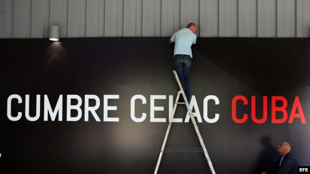 Workers put finishing touches on a sign of the Second Summit of the Community of Latin American and Caribbean States (CELAC).