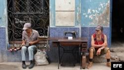 Un hombre repara zapatos, mientras otro vende una vieja máquina de coser hoy, viernes 15 de abril de 2016, en La Habana (Cuba), un día antes del inicio del VII Congreso del Partido Comunista de Cuba (PCC).
