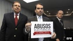 """Tomás Guanipa (c), diputado del partido Primero Justicia de Capriles, muestra un cartel con el lema """"Abusos electorales""""."""