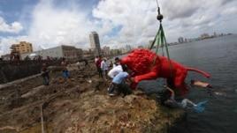 El artista plástico cubano Roberto Favelo (i) posa junto a un león rojo creado por él que conforma la obra