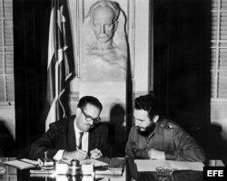 El presidente de Cuba, Osvaldo Dorticós (izda), firma la resolución del gobierno revolucionario que dispone la nacionalización de los bancos norteamericanos radicados en Cuba. A su lado, el primer ministro Fidel Castro (dcha).