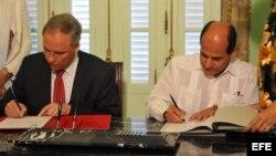 El director general de Asuntos Políticos del ministerio de Asuntos Exteriores de Holanda, Karel Van Ooesterom (i) y el vicecanciller cubano, Rogelio Sierra (d), firman una declaración política sobre cooperación bilateral.