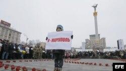 """Un niño sostiene un cartel con el lema 'Yo soy Mariupol"""" en una manifestación por las víctimas del bombardeo de un autobús civil en Volnovaja."""