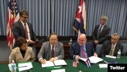 Funcionarios de EEUU y Cuba firman el acuerdo en Washington.
