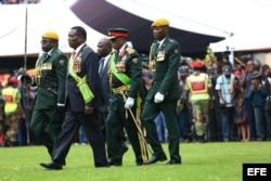 Mnangagwa (2i), camina junto a varios oficiales durante su ceremonia de juramento oficial.