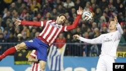 El jugador del Atlético de Madrid Juanfran Torres disputa el balón con Cristiano Ronaldo