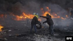 Unos manifestantes lanzan cócteles molotov a la polícia durante los enfrentamientos en el centro de Kiev, Ucrania.