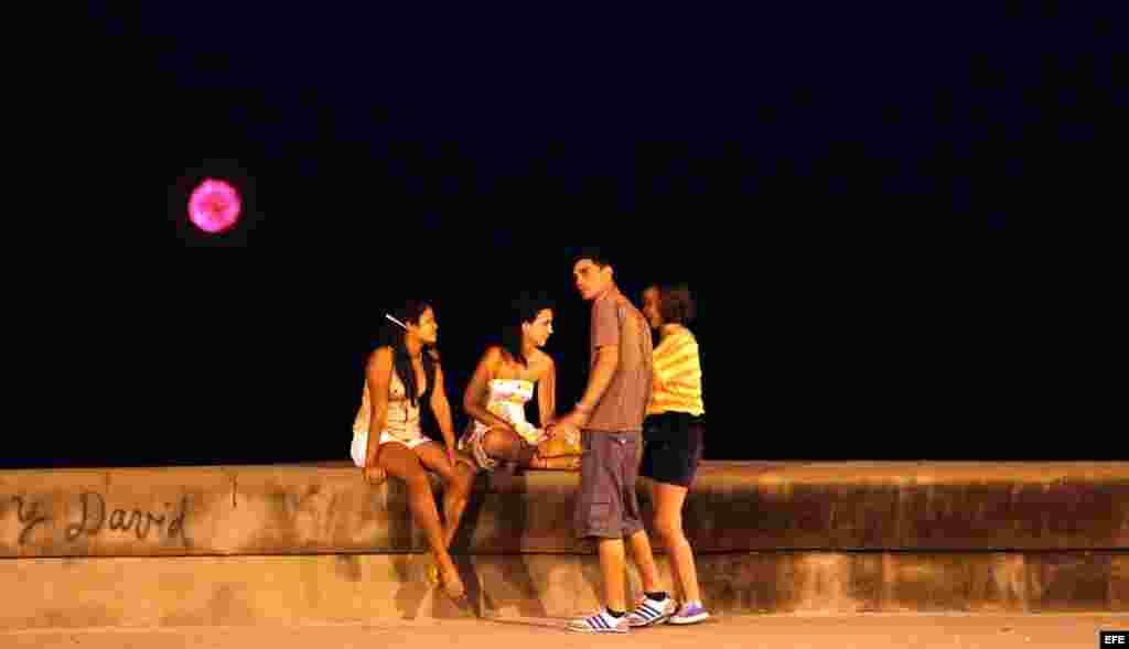 Jóvenes conversan mientras en el fondo se observan los fuegos artificiales lanzados por una flotilla del exilio cubano para conmemorar el vigésimo aniversario del hundimiento del Remolcador 13 de marzo.