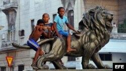 Varios niños juegan en la estatua de un león en el Paseo del Prado de La Habana (Cuba).