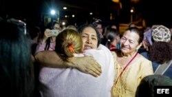 La opositora venezolana María Pérez abraza a sus familiares luego de su liberación, en las inmediaciones de 'El Helicoide'.