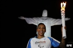 La medallista olímpica Rafaela Silva, carga la antorcha Paralímpica Río 2016, con el Cristo Redentor al fondo.