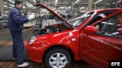 Trabajador chino inspeccionando un vehículo del grupo Geely en su planta de Ningbo (China).