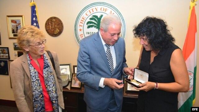 El alcalde de Miami, Tomás Regalado (c), entrega la llave dorada de la ciudad a la cantautora española Rosana (d) acompañado de la cónsul general de España en Miami, María Cristina Barrios Almazor (i).