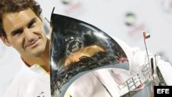 Federer sostiene el trofeo que le entregaron tras ganar por séptima vez el torneo de tenis de Dubai.
