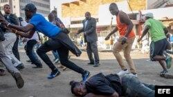 Un hombre cae al suelo tras ser disparado en la espalda por las fuerzas de seguridad durante una protesta organizada por simpatizantes del Movimiento por el Cambio Democrático (MDC) contra el conteo de votos tras las elecciones del país, en Harare, Zimbabue, el 1 de agosto de 2018.