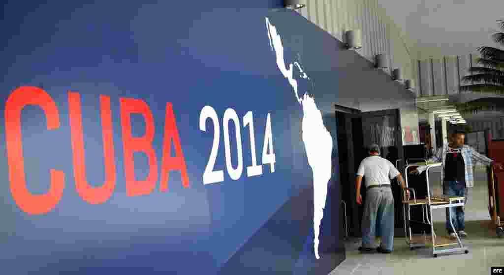 Dos hombres ingresan muebles al salón principal de Pabexpo, sitio donde se celebrará próximamente la II Cumbre de la Comunidad de Estados Latinoamericanos y del Caribe (CELAC).