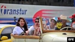 Turistas se toman una selfie durante un paseo en un auto clásico en La Habana.