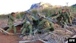 Soldados cubanos desenmascaran una pieza de artillería.