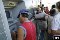 Un hombre extrae dinero de un cajero automático en un banco de La Habana.