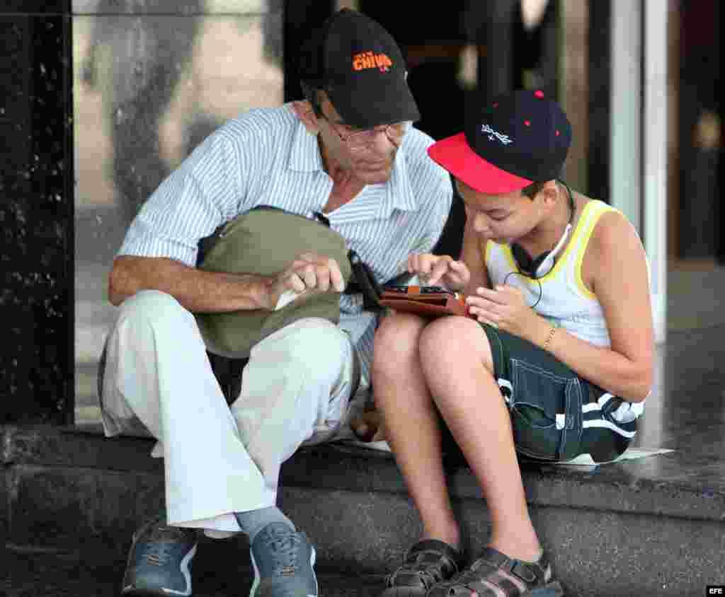 Dos personas navegan por internet desde un dispositivo móvil hoy, viernes 3 de julio del 2015, en una de las zonas habilitadas con Wi-Fi en La Habana.