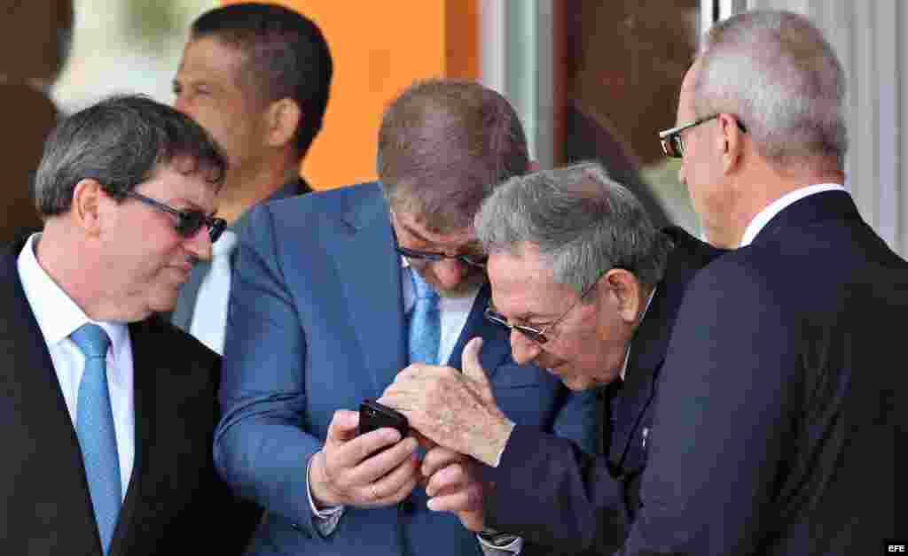 Raúl Castro observa el teléfono móvil del embajador ruso en Cuba, Mijail Kaminin.