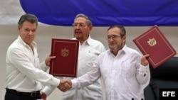 """El delegado de las FARC en Cuba, Rodrigo Londoño Echeverri, alias """"Timochenko"""" (d) y el presidente de Colombia, Juan Manuel Santos (i) junto a el presidente de Cuba, Raúl Castro (c) sostienen en sus manos el acuerdo de paz."""