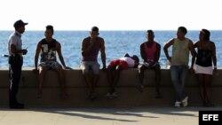 Un policía junto a varios jóvenes en el malecón de La Habana (Cuba). Foto Archivo.