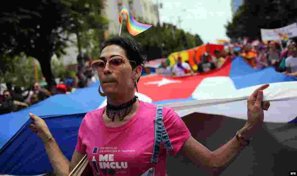 """Una mujer trans sostiene una bandera cubana gigante durante una """"conga"""" contra la homofobia y la transfobia en La Habana."""