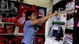 Una mujer de la Liga Nacional por la Democracia (NLD) cuelga un calendario con la fotografía de la opositora birmana Aung San Suu Kyi y el presidente de Estados Unidos en la tienda de recuerdos del partido en Rangún (Birmania).