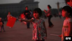 Una niña sujeta una bandera china en la plaza de Tiananmen, en Pekín (China), hoy, martes 4 de junio de 2013.