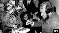"""El escritor soviético Alexander Solzhenitsyn, rodeado de periodistas y fotógrafos, firma autógrafos en el libro """"El Archipiélago Gulag"""", en la oficina de su editor en París."""