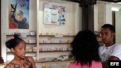 Tres jóvenes conversan en una farmacia en La Habana,Cuba.