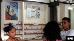 Tres jovenes conversan en una farmacia en La Habana,Cuba.