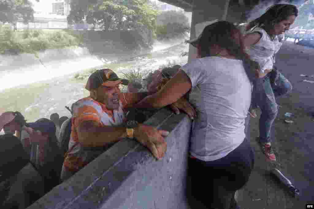 Una mujer ayuda a un hombre a subir de una pendiente a la orilla de una vía durante una protesta en contra del Gobierno venezolano hoy, miércoles 19 de abril de 2017, en Caracas (Venezuela). Centenares de opositores en distintos puntos de caracas se enfre