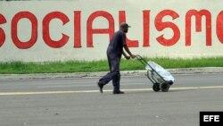 Un hombre camina frente a un cartel alusivo al socialismo en La Habana.