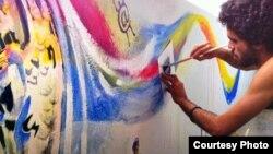 El Sexto pinta una pared en Miami con uno de sus grafitis.