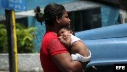 Una cubana carga a su hijo pequeño.
