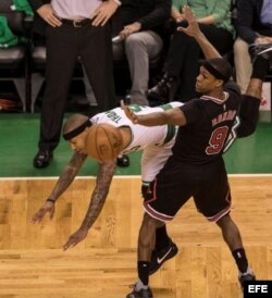 Isaiah Thomas (i) de Celtics choca con Rajon Rondo (d) de Bulls.