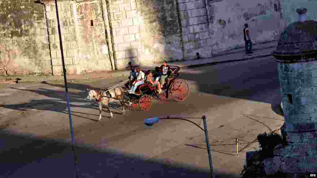 Varios turistas pasean en un coche de caballos por una avenida de La Habana Vieja.