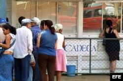 Varias personas hacen cola frente a una Casa de Cambio (CADECA).