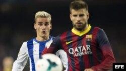 El defensa del FC Barcelona Gerard Piqué (d) y el centrocampista francés de la Real Sociedad Antoine Griezmann durante el partido de la sexta jornada de Liga de Primera División disputado esta tarde en el Camp Nou.